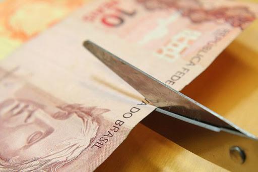 Tesoura cortando uma nota de 10 reais ao meio