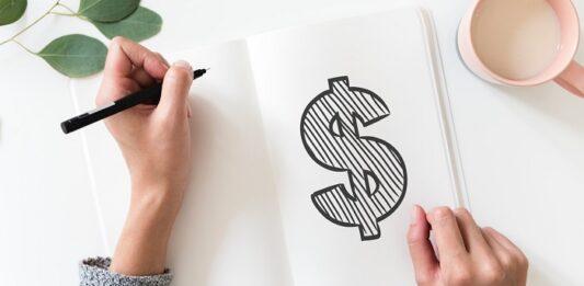 Pessoa desenhando um cifrão em um caderno com xícara ao lado