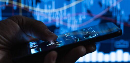 Pessoa acessando investimentos pelo celular com um telão com gráficos ao fundo