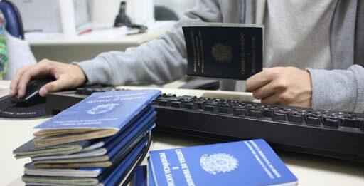 Pessoa com várias carteiras de trabalho acessando computador