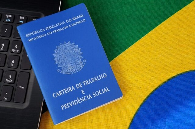 Parte de um teclado com um carteira de trabalho em cima de uma parte da bandeira do Brasil