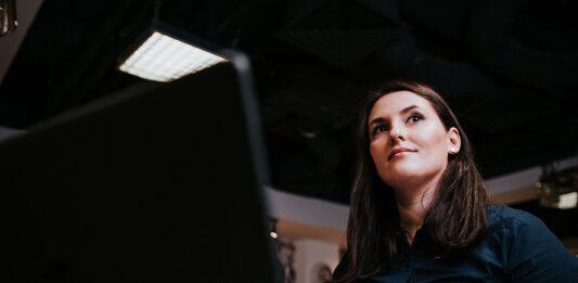 Mulher segurando um papel em frente a um computador
