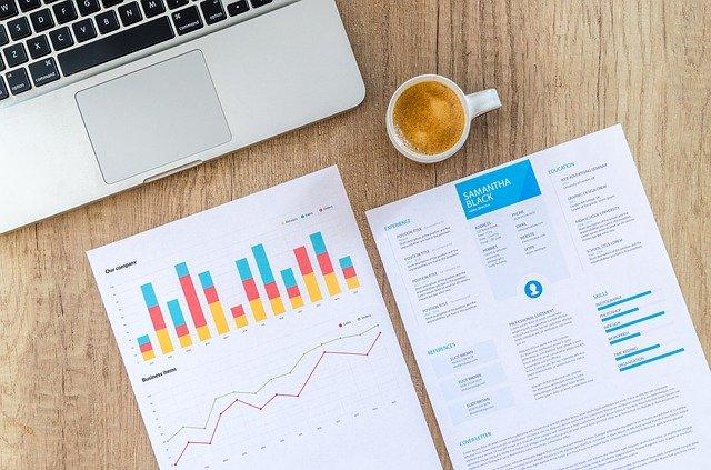 Folhas com gráficos, xícara de café e notebook em uma mesa de trabalho