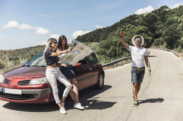 Três amigos na estrada ensolarada lendo um mapa encostados em um carro vermelho