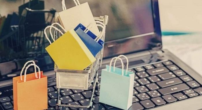 Sacolas pequenas de compras coloridas em cima de um carrinho de compras que está em um teclado preto de notebook para Direitos do Consumidor