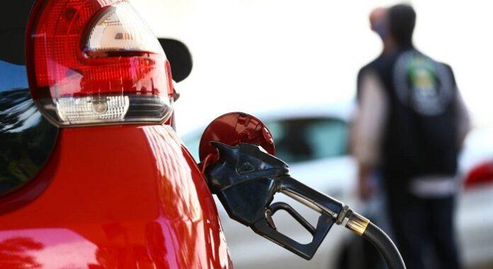 Carro vermelho sendo abastecido em um posto de combustível