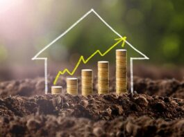 Montagem de casa feita de giz numa terra com fileiras de moedas e um gráfico em amarelo em forma de seta