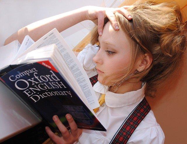 Criança lendo o dicionário de Oxford