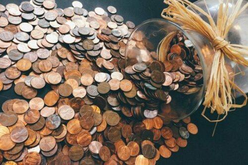 juntar mil reais: pote com moedas espalhadas em uma mesa