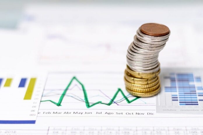Uma fileira de moedas em cima de uma folha com gráficos