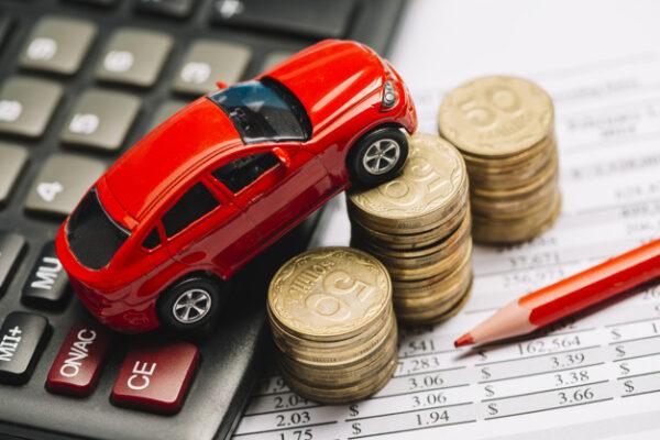 Carro vermelho em miniatura em cima de uma calculadora e 3 fileiras de moedas ao lado com um lápis vermelho