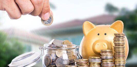 Mão colocando moeda de um real em um pote com fileiras de moedas e cofre ao lado