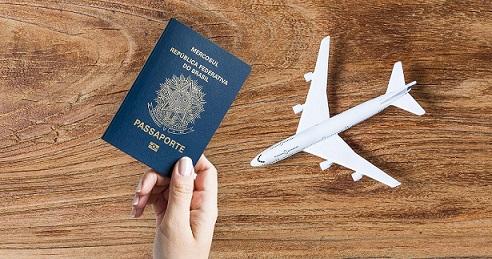 Mão feminina segurando passaporte e um avião de miniatura do lado