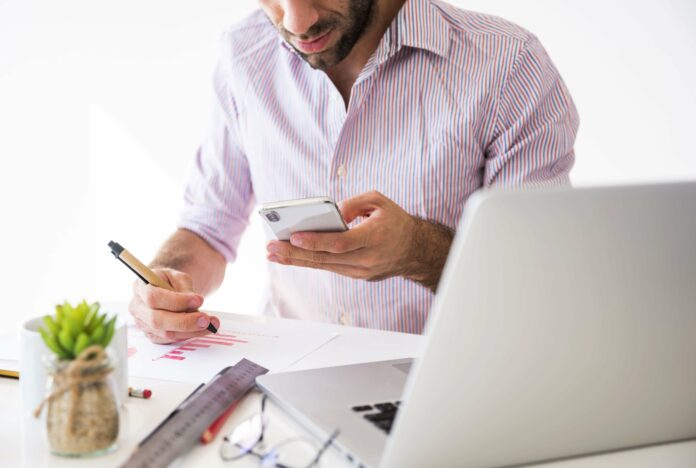 Homem escrevendo com celular na mão com notebook