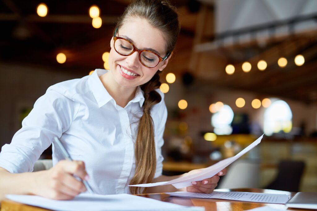 Loira de óculos vestida de branco sorrindo e escrevendo