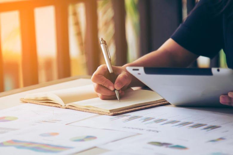 pessoa escrevendo em um caderno e utilizando o tablet