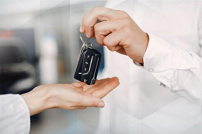 Pessoa entregando chave do carro para outra