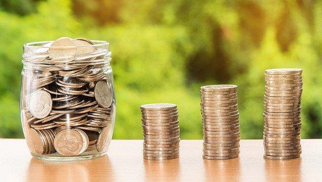 Pote transparente cheio de moedas e três fileiras de moedas do lado de fora