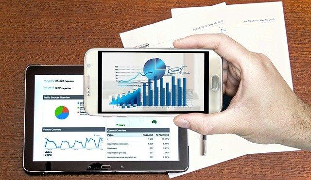 Mão de uma pessoa segurando um celular com tela de gráficos. Ao fundo, tablet e papéis com gráficos