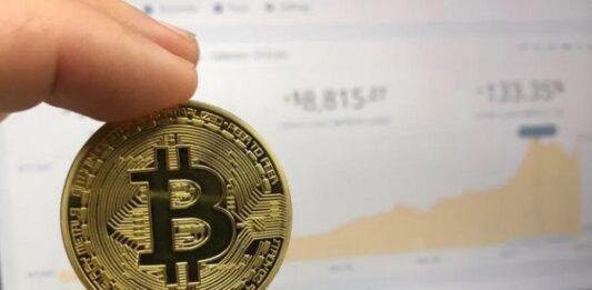 Pessoa segurando uma moeda de bitcoin
