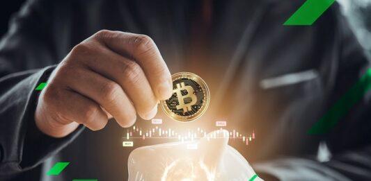 homem depositando uma criptomoeda Bitcoin em um cofre
