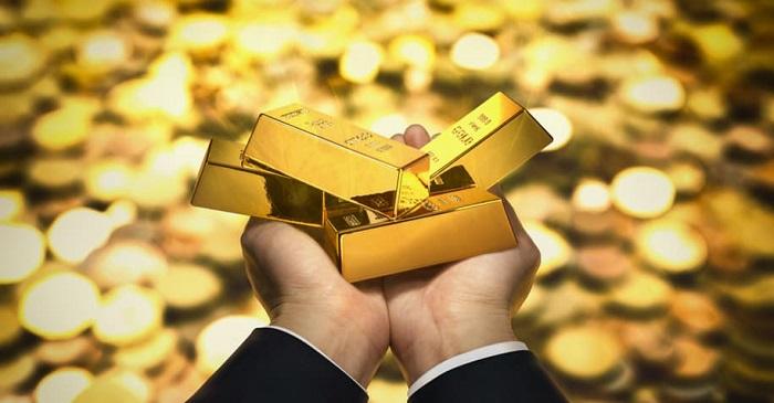 mão com quatro barras de ouro