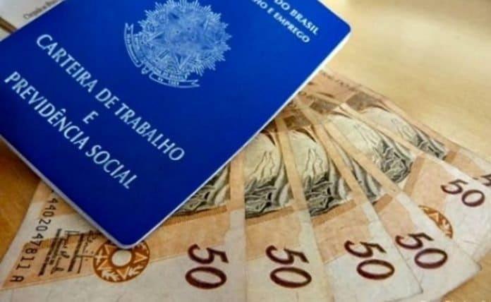 adiantamento 13º salário: carteira de trabalho e cinco notas de cinquenta reais