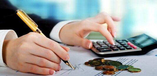 Mulher realizando cálculo com calculadora e moedas na mesa