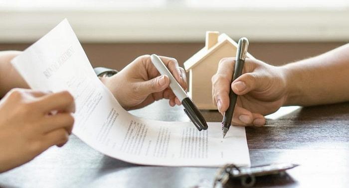 duas pessoas escrevendo em um papel com canetas