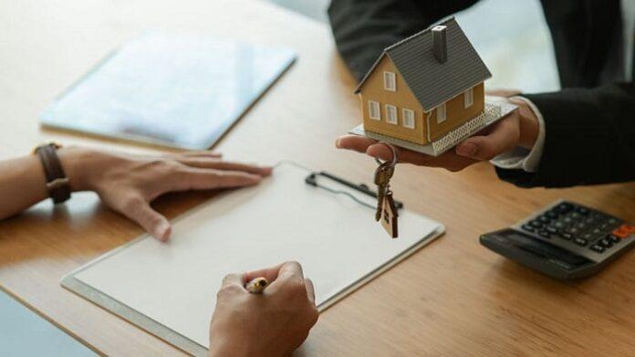 Pessoa escrevendo e outra com uma pequena casa amarela em uma das mãos