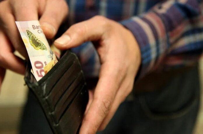 Homem guardando dinheiro dentro de uma carteira preta