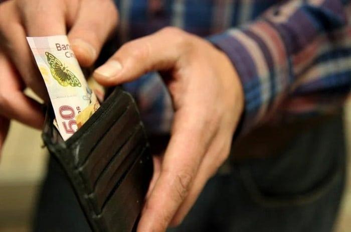 pessoa retirando nota de cinquenta pesos argentinos de uma carteira preta