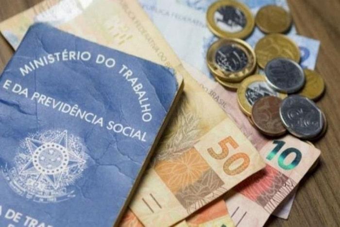 carteira em cima de notas de cinquenta e dez reais com algumas moedas ao lado