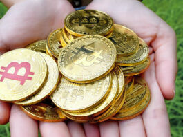 Mão segurando várias criptomoedas Bitcoin