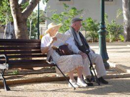 dois idosos sentando em um banco de praça