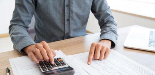 Homem mexendo na calculadora com planilhas