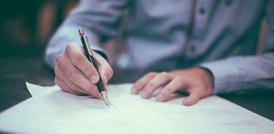 Homem assinando contrato de um consórcio