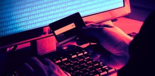 Homem segurando cartão de crédito e acessando computador