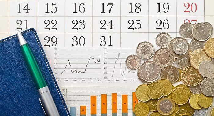 imagem de um calendário com caneta, bloco e moedas