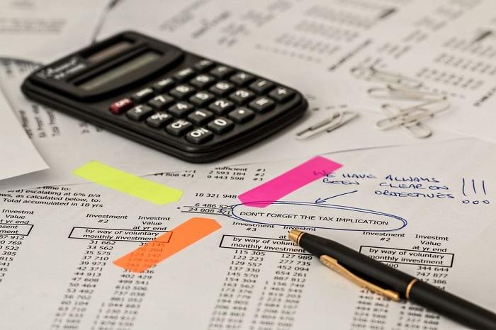 papel com cálculos e várias anotações e uma calculadora