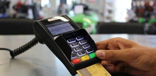 Máquina de cartão de crédito com uma pessoa segurando e um cartão inserido