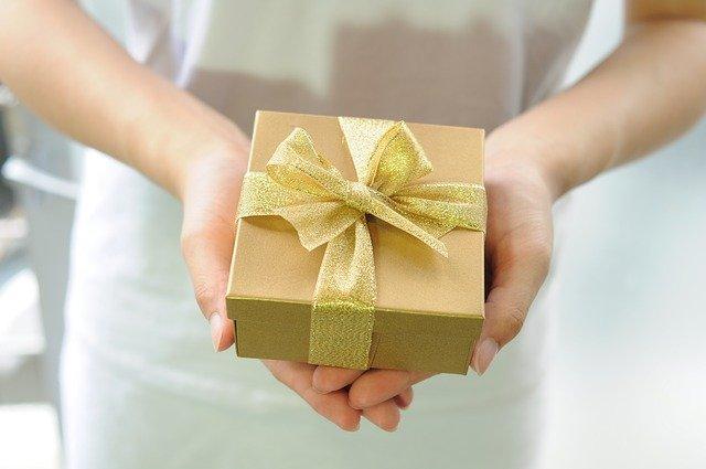 mulher segurando um embrulho dourado de presente