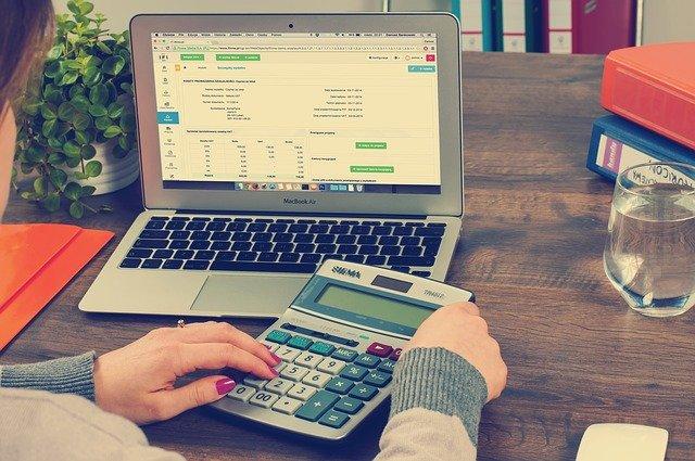 Mulher em frente do notebook usando calculadora