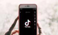 Mão segurando um celular com a tela do TikTok