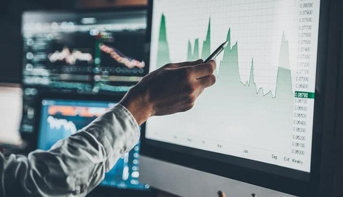 Homem medindo gráfico de um FIDC em uma tela grande
