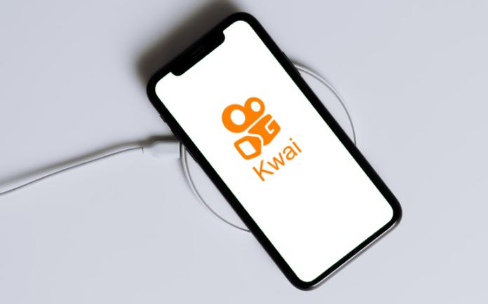 Celular com a logo do Kwai na tela