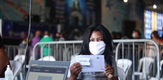 Mulher de máscara protetora branca beneficiada pelo Supera Rio mostrando o cartão