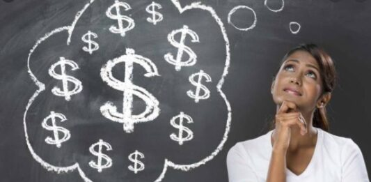 Mulher ao lado de um balão de pensamento com cifrões de dinheiro desenhados em giz num quadro negro