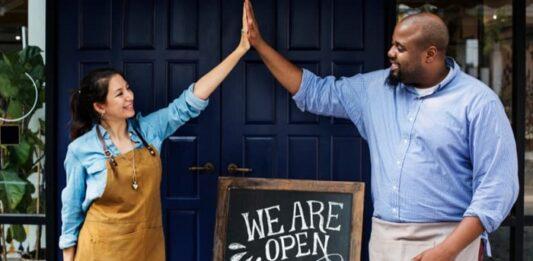 Mulher e homem de avental segurando mãos em frente de uma loja
