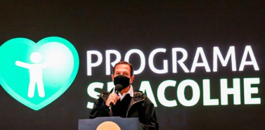 Governador João Dória de máscara preta falando no microfone